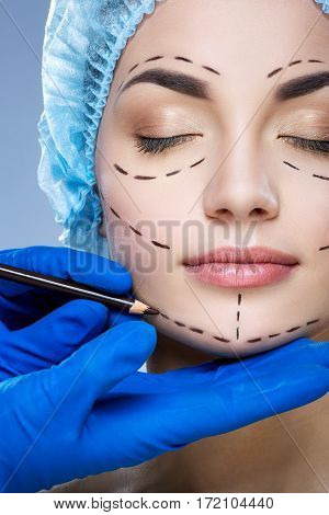 Attractive girl with dark eyebrows wearing blue medical hat at studio background, doctor's hand making perforation lines on patient's face.