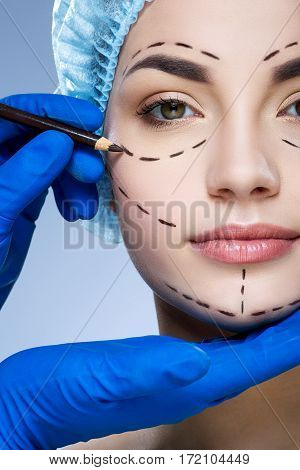 Young girl with dark eyebrows wearing blue medical hat at studio background, doctor's hand making marks on patient's face, portrait, perforation lines on face.