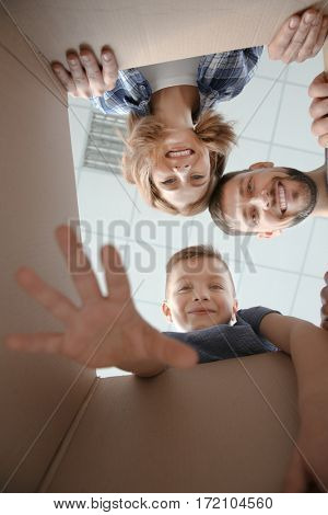 Happy family looking through box. Moving concept
