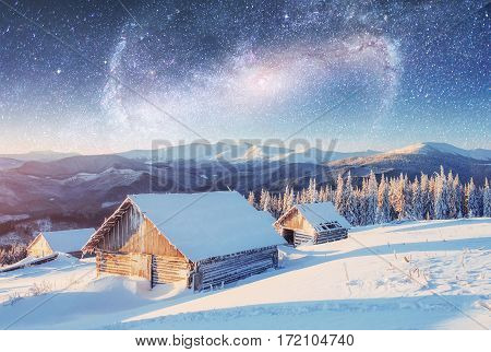 chalets in the mountains at night under the stars. Courtesy of NASA. Magic event in frosty day. In anticipation of the holiday. Dramatic scenes. Carpathians, Ukraine, Europe