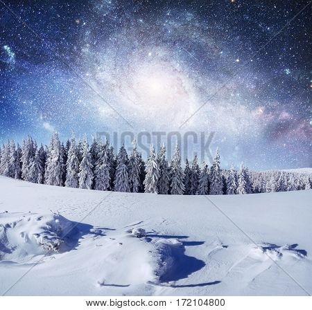 starry sky in winter snowy night. fantastic milky way in the New Year's Eve. Courtesy of NASA. In anticipation of the holiday. Dramatic scene. Carpathian. Ukraine.