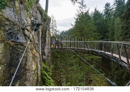 Vancouver Canada - January 28 2017: A suspension bridge hanging from a cliff face high above the canyon at the Capilano Suspension Bridge Park