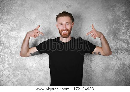 Man in black T-shirt on colour textured wall background