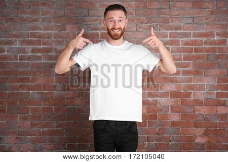 Young handsome man in white T-shirt on brick wall background