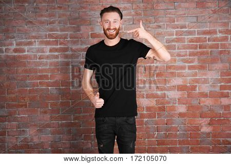 Young handsome man in black T-shirt on brick wall background