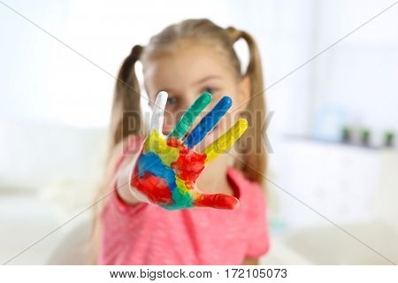 Cute little girl with hands in paint in the room