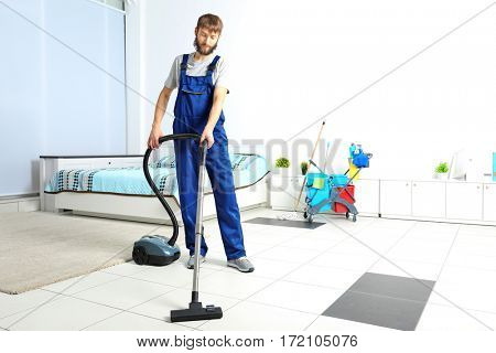 Funny young man hoovering floor with vacuum cleaner at home