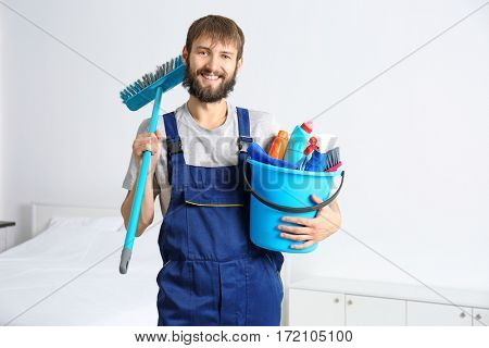 Funny young man with cleaning supplies at home