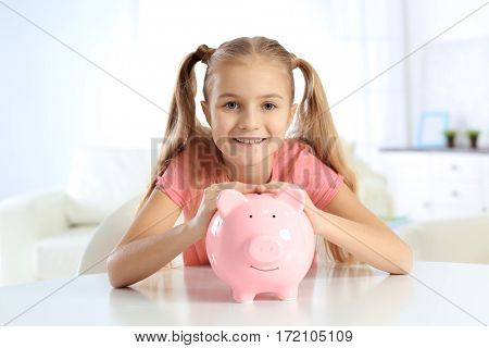 Cute little girl with piggy bank sitting at table