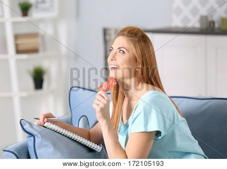 Beautiful young woman calculating taxes at home