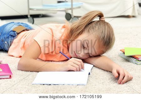 Attractive tired little girl lying on the floor with copybook