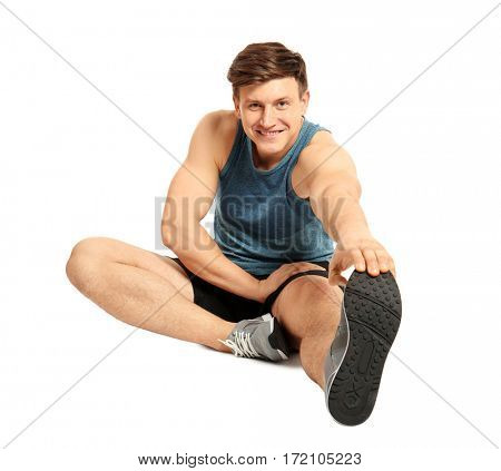 Young handsome sportsman doing exercises on white background