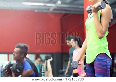 Athletic woman training with dumbbells in gym