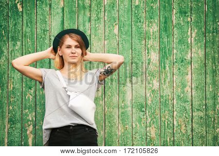 Trendy young woman with leather clutch on green wooden background