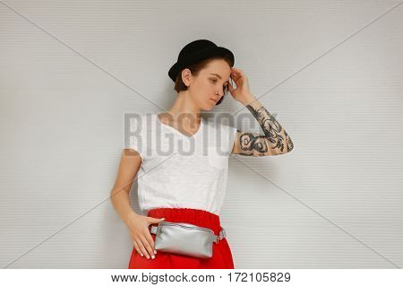 Stylish young woman with silver clutch on light background