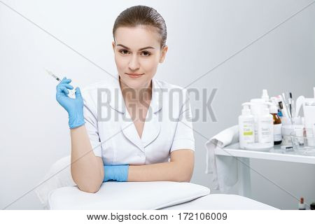 Doctor standing near couch and holding syringe. Looking at camera, smiling. Cosmetological clinic. Medical equipment. Healthcare, clinic, cosmetology