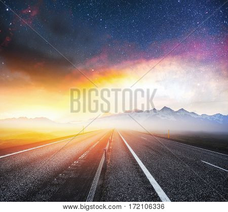 Starry Sky over the mountains. The asphalt road with white markings. Beautiful summer landscape. Soft filtering effect. Europe