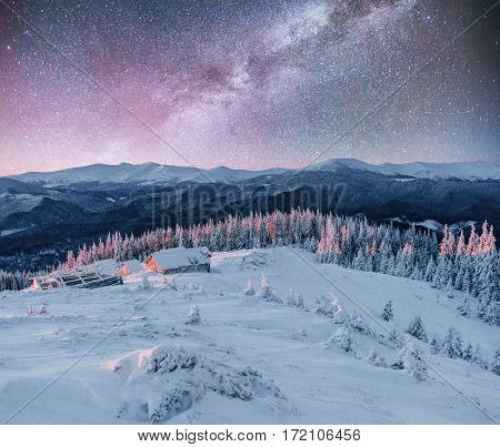 Cabin in the mountains in winter. Mysterious fog. In anticipation of holidays. Fantastic starry sky and the milky way. Carpathians. Ukraine, Europe