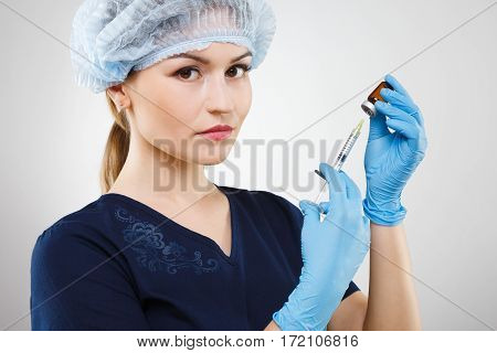 Lovely nurse with nude make up wearing blue medical uniform, medical hat and gloves at gray background, holding syringe.