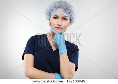 Thoughtful nurse with nude make up wearing blue medical uniform, medical hat and gloves at gray background, portrait.
