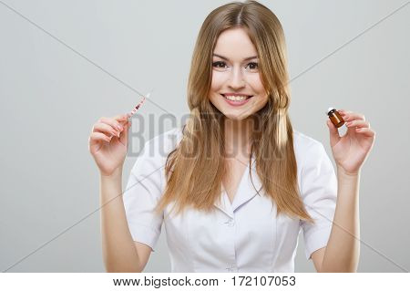 Happy nurse with brown hair and nude make up wearing white medical robe at gray background and posing with syringe, portrait.