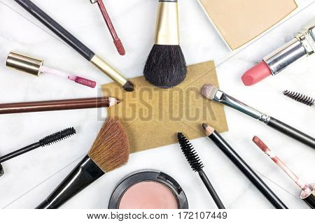 Makeup brushes, pencils, lipstick et al on a light background, with a blank kraft business card for copy space. A horizontal template for a makeup artist's business card or flyer design