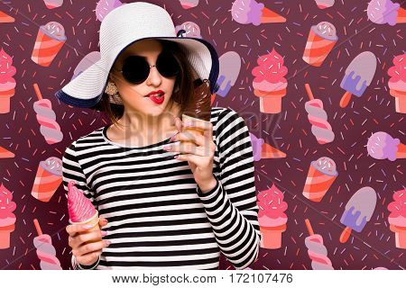 Pretty brunette girl, wearing in striped blouse, black sunglasses and white hat, is posing with two ice cream, on orange background, in studio, waist up