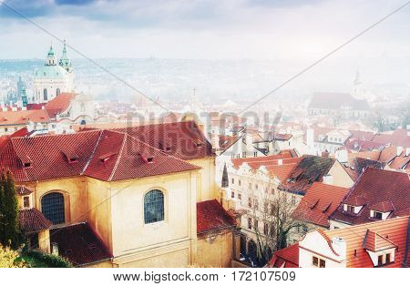 The red roof in Prague. Panoramic view of Prague from Prague Castle, Czech Republic. Summer day with blue sky with clouds and dense fog in the city