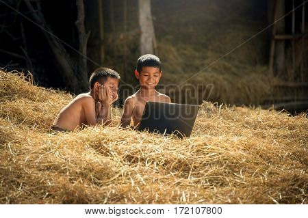 Children using laptop computer in Asia countryside.