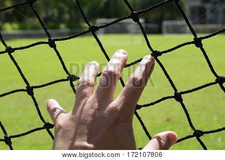 Man's hand extended to touch the mesh of a football field.