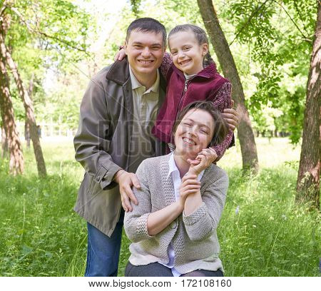Happy family and child portrait. City park in summer season. Beautiful landscape with trees and green grass