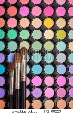 Make-up brushes on colorful eyeshadow make-up palette with copyspace. Flat lay