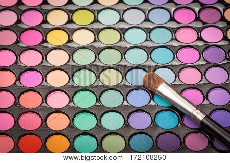 Makeup brush on colorful eyeshadow makeup palette with copyspace. Beauty background