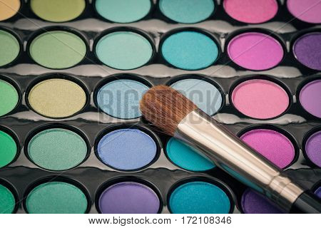 Close-up of make-up brush on colorful eyeshadow palette