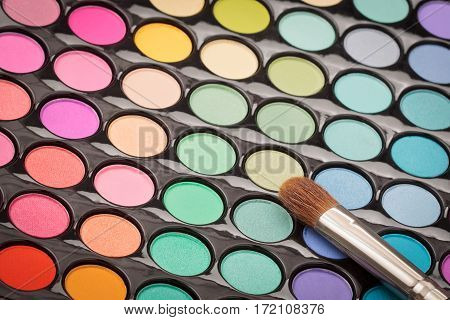 Beautiful makeup background. Makeup brush on colorful makeup palette with copyspace