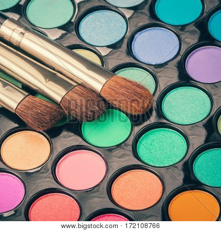 Set of makeup brushes on colorful eyeshadow palette