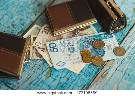 Polish Zloty With Wallets On The Old Wooden Background