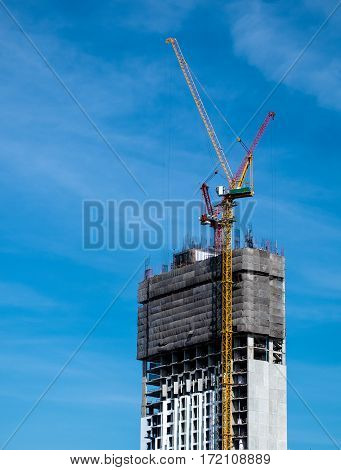 Industrial construction crane for high rise building with blue sky background