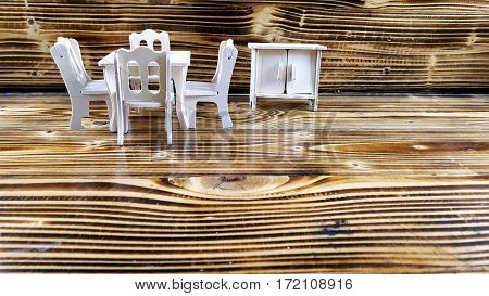 DIY project of home concept mini wooden toy table chairs and closet on wooden texture as background.