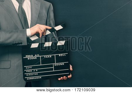 Young man holding clapper board on black background
