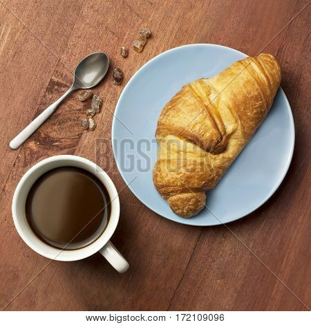 A square photo of a cup of black coffee with a croissant on a blue plate, on a wooden board texture, shot from above, with cane sugar and a spoon