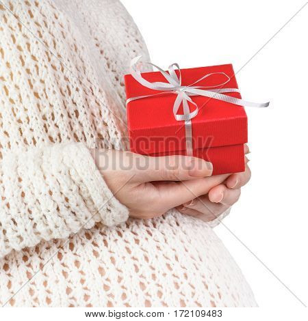 Closeup of pregnant woman wearing knitted sweater holding red gift box isolated on white background