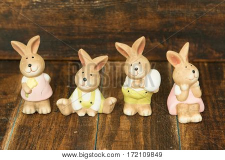 Four ceramic painted rabbits for Easter decoration on a wooden background