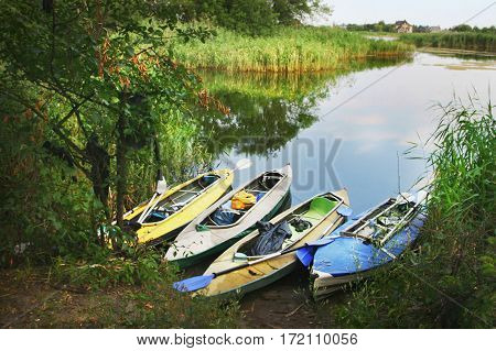Four Colored Boats  On The Shore Of Small River