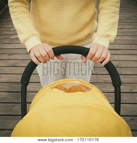 Closeup shot of young mother strolling a carriage