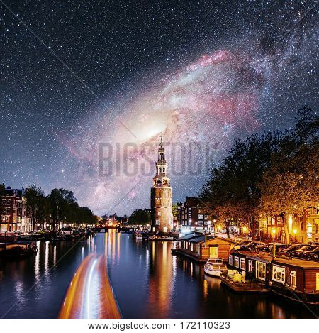 Beautiful night in Amsterdam. Night illumination of buildings and boats near the water in the channel. Fantastic starry sky and the milky way. Courtesy of NASA.