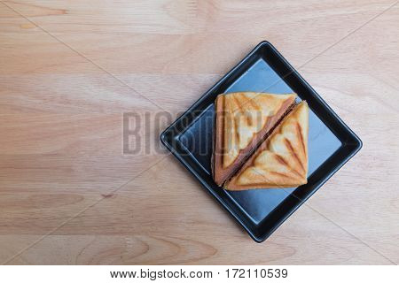 Ham cheese toast in black rectangle disk on the plywood tabe.
