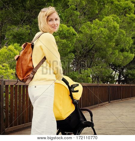 Smiling young mother strolling with newborn in carriage. Blonde hair woman walking in park with stroller