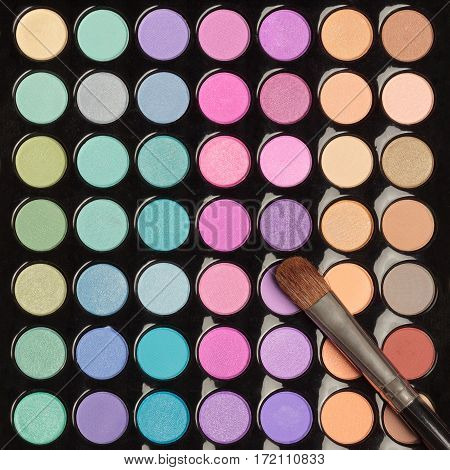 Closeup of colorful eyeshadow palette with makeup brush. Flat lay