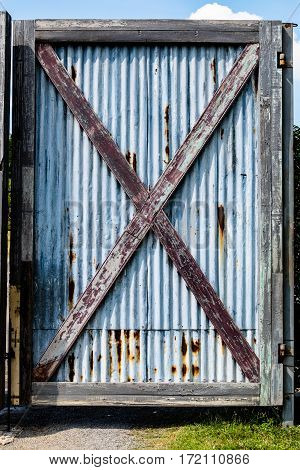 Old barn wooden bracing frame with zinc sheet door.
